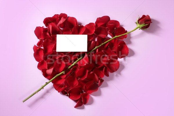 Cupid arrow in a red rose petals heart shape Stock photo © lunamarina