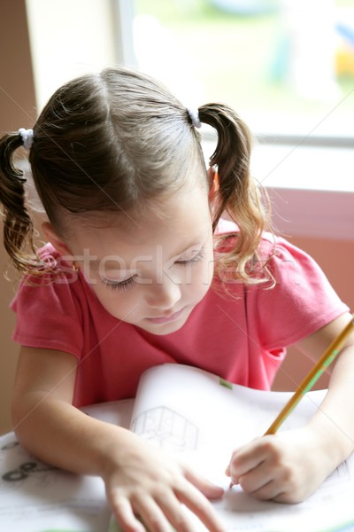 Little toddler girl writing at school desk Stock photo © lunamarina