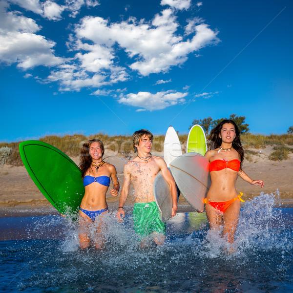Teenager surfers group running beach splashing Stock photo © lunamarina