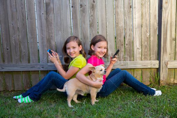 Tweeling zus meisjes spelen smartphone hond Stockfoto © lunamarina