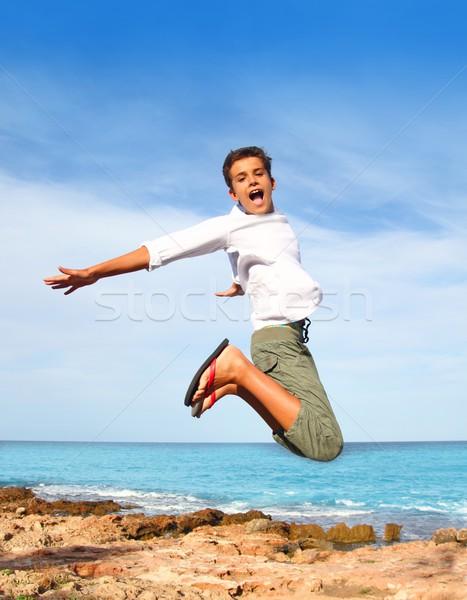 Stock photo: boy teenager high fly jump on beach blue sky