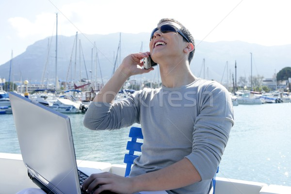 Businessman working with computer on a boat Stock photo © lunamarina