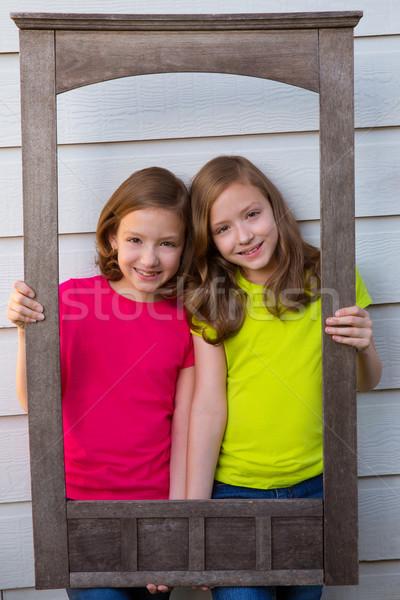 Twin sister girls posing with aged wooden border frame Stock photo © lunamarina