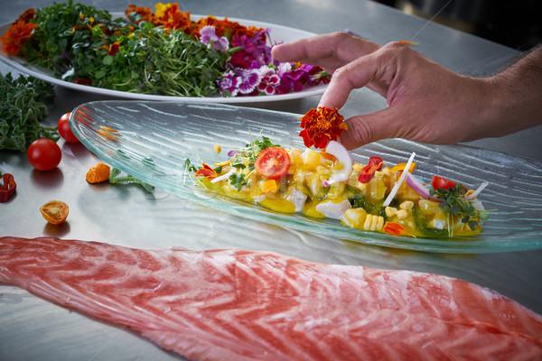 Chef hands garnishing flower in ceviche dish Stock photo © lunamarina