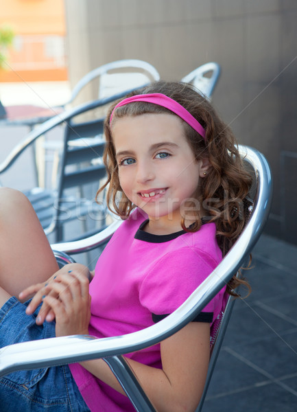 Smiling girl sitting in outdoor aluminium chair Stock photo © lunamarina