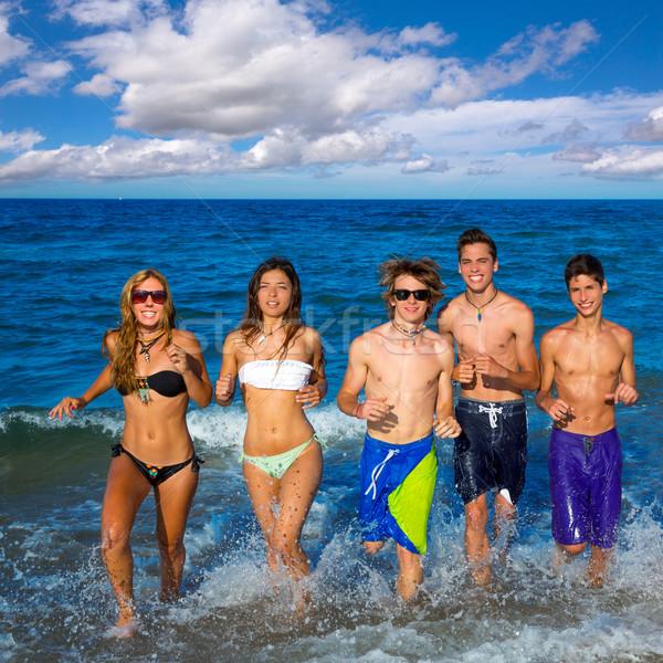 Teens group running happy splashing on the beach Stock photo © lunamarina