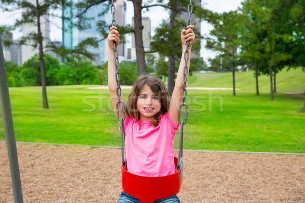 Brunette kid girl playing with swing on city park Stock photo © lunamarina