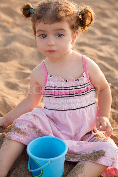 Blu eyes brunette toddler girl playing with sand in beach Stock photo © lunamarina