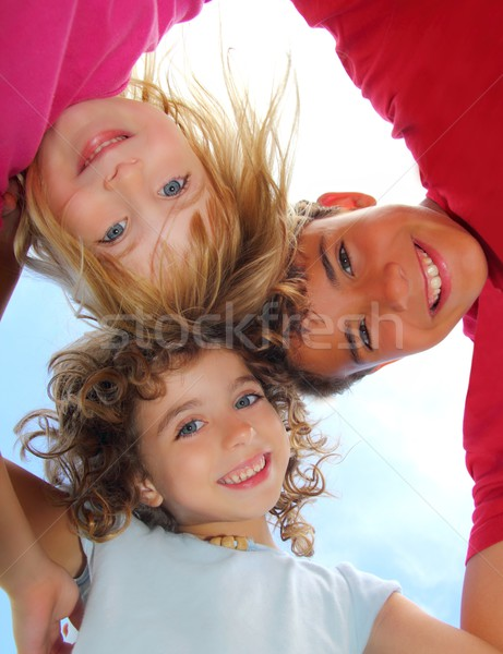 Below view of happy three children embracing Stock photo © lunamarina