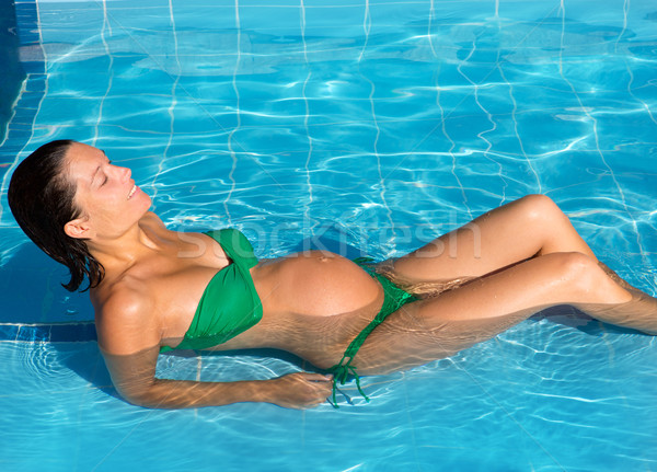 Beautiful pregnant woman sun tanning at blue pool Stock photo © lunamarina