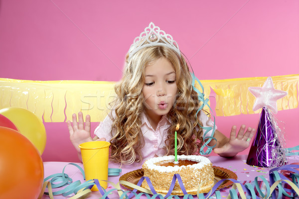 happy little blond girl blowing cake candle in a birthday party Stock photo © lunamarina