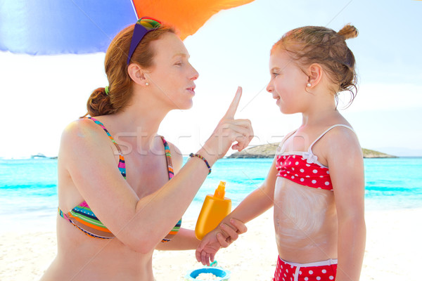 daughter and mother in beach with sunscreen Stock photo © lunamarina