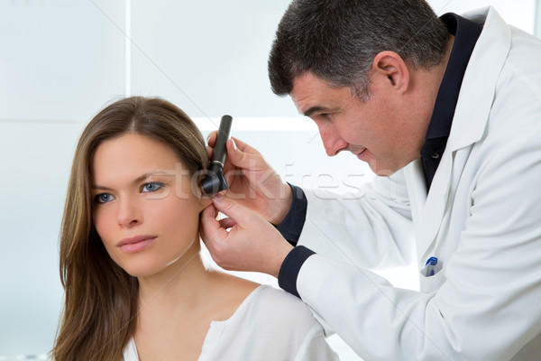 Doctor ENT checking ear with otoscope to woman patient Stock photo © lunamarina