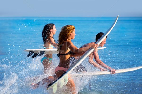 Boys and girls teen surfers running jumping on beach Stock photo © lunamarina