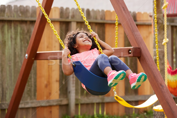 Kid toddler girl swinging on a playground swing Stock photo © lunamarina