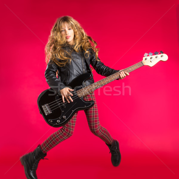 Blond Rock and roll girl with bass guitar jump on red Stock photo © lunamarina