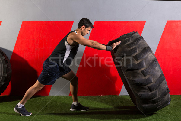 man flipping a tractor tire workout gym exercise Stock photo © lunamarina