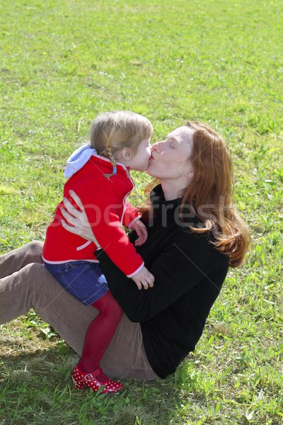 mother and daugther kissing lips in meadow Stock photo © lunamarina