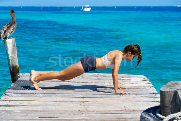 Latin woman push up workout in beach pier Stock photo © lunamarina