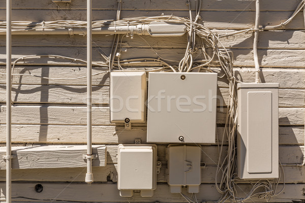 Messy cables and electrical boxes in a wooden beige wall Stock photo © lunamarina