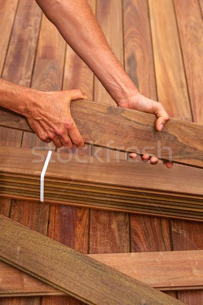 Ipe deck installation carpenter hands holding wood Stock photo © lunamarina
