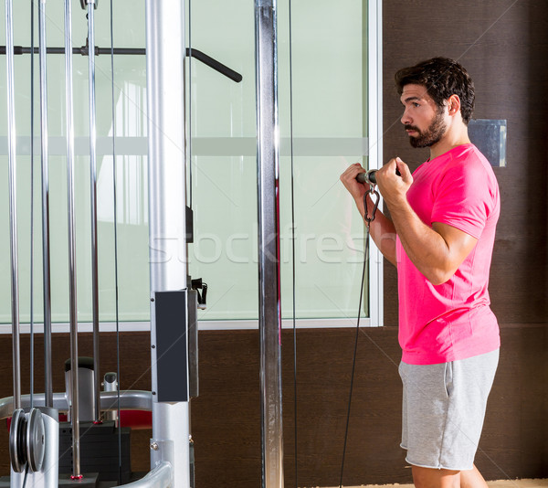 Standing biceps cable curl man in pulley machine Stock photo © lunamarina