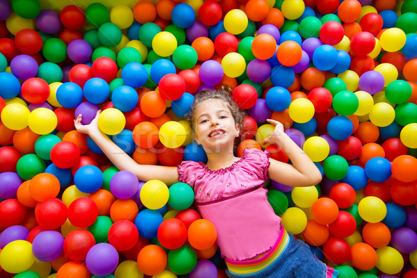 child girl on colorful balls playground high view Stock photo © lunamarina