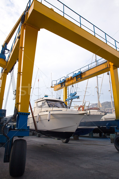 Boat wheel crane elevating motorboat to yearly paint Stock photo © lunamarina
