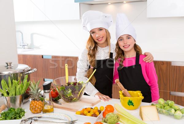 Kid girls junior chef friends hug together at cooking school Stock photo © lunamarina