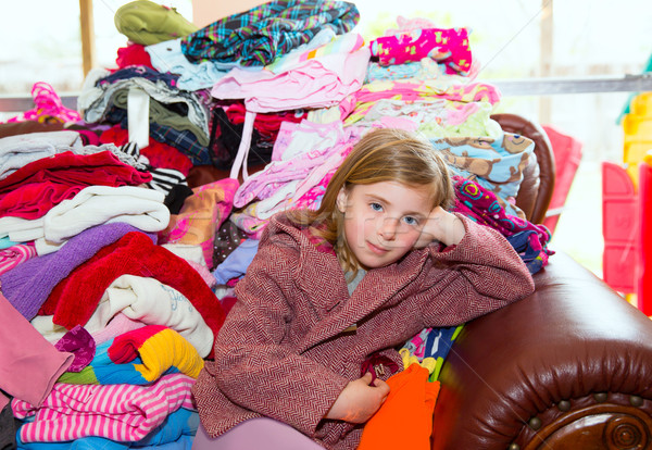 Blond kid girl sitting on a messy clothes sofa Stock photo © lunamarina