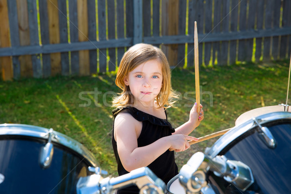 Drummer blond kid girl playing drums in tha backyard Stock photo © lunamarina