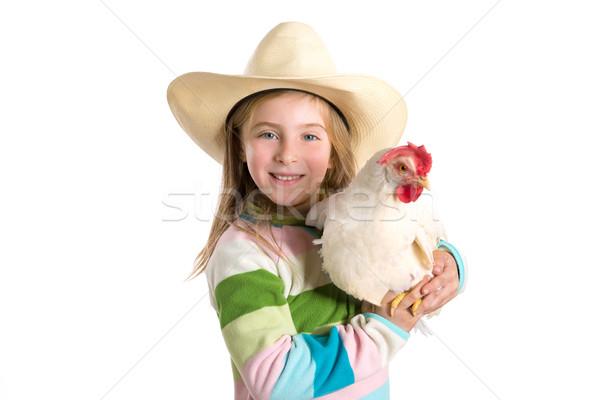 Blond kid girl farmer holding white hen on arms Stock photo © lunamarina