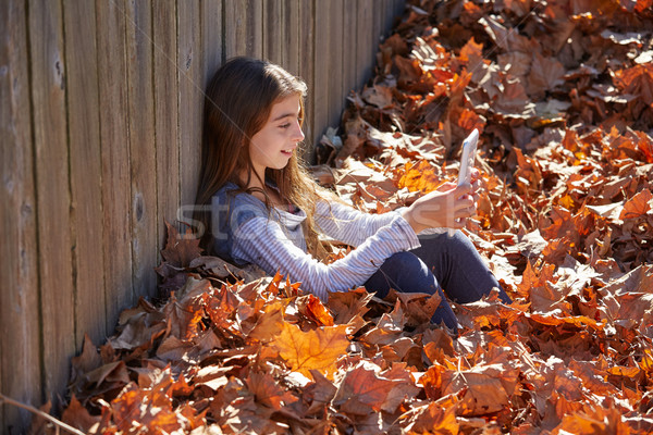 Kid girl playing tablet pc in autumn leaves Stock photo © lunamarina