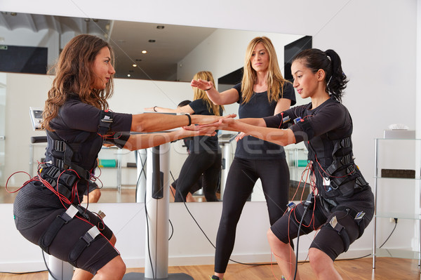 Stock photo: EMS electro stimulation women exercises