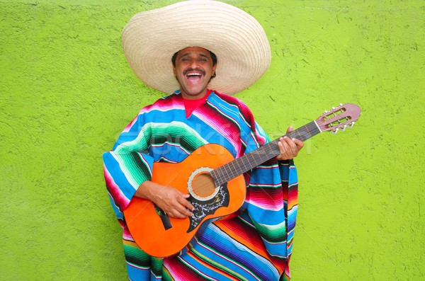 Mexican typical man playing guitar poncho Stock photo © lunamarina