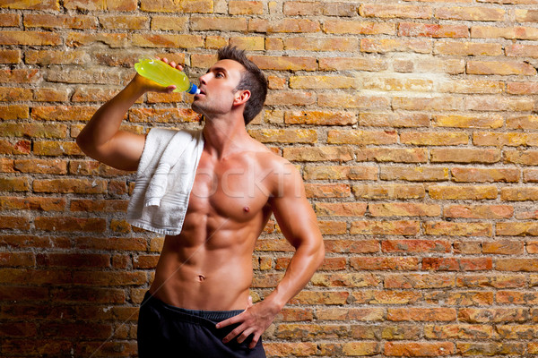 muscle shaped man at gym relaxed drinking Stock photo © lunamarina