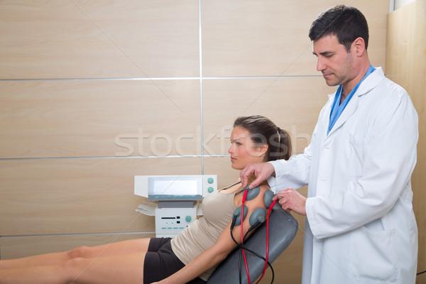 Doctor therapist checking muscle electrostimulation to woman Stock photo © lunamarina