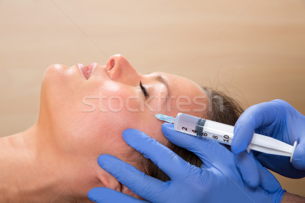 Anti aging facial mesotherapy syringe on woman face Stock photo © lunamarina