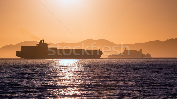Alcatraz island penitentiary at sunset and merchant ship Stock photo © lunamarina