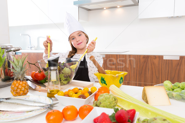 Blond kind girl junior chef on countertop salad Stock photo © lunamarina