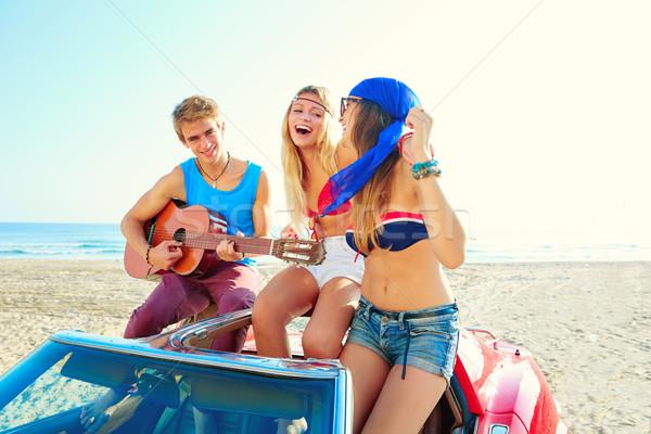 young group having fun on beach playing guitar Stock photo © lunamarina