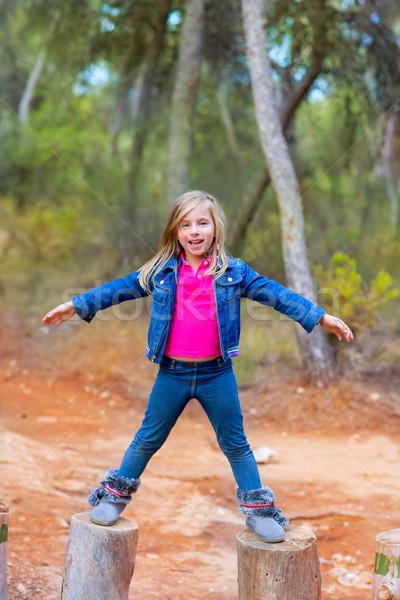 kid girl climbing tree trunks with open arms Stock photo © lunamarina