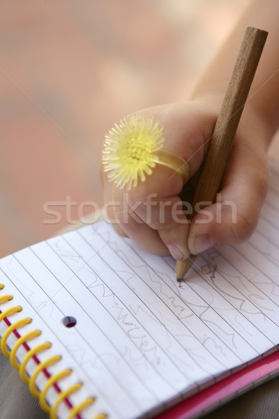 Stock photo: Children hand with funny  yellow ring writing on a notebook