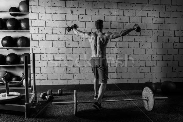 gym man rising hex dumbbells weightlifting rear Stock photo © lunamarina