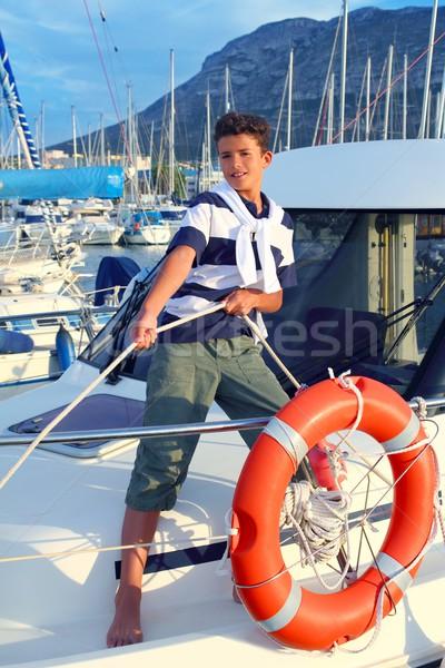 Boy teen sailor mooring boat rope in harbor Stock photo © lunamarina