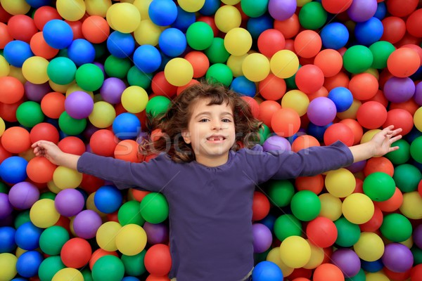 Stock photo: colorful balls funny park little girl lying gesturing