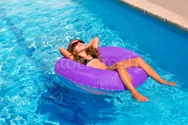 Stock photo: children girl relaxed on purple inflatable pool ring