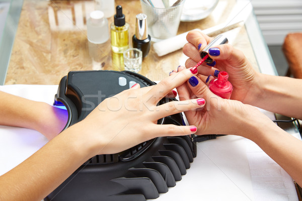 Nails painting with UV dry lamp in blue light Stock photo © lunamarina