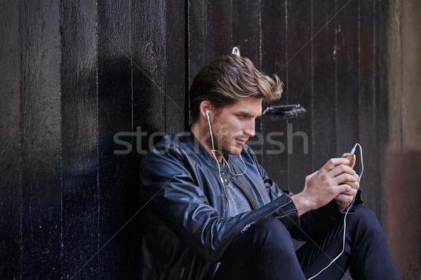 Fiatalember hallgat zene okostelefon fülhallgató ül Stock fotó © lunamarina