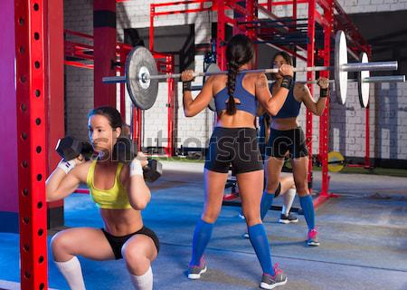Crossfit woman kick boxing with red punching bag Stock photo © lunamarina